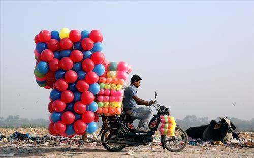 продавач носи пластични топки во Индија