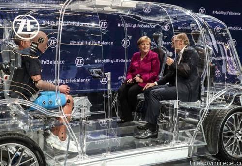 меркел во стаклен автомобил на изложба на автомобили во Франкфурт
