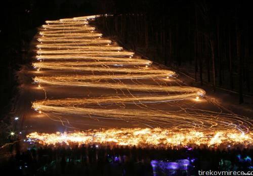 стотици скијачи со факели во раце минуваат по снежна патека во рускиот град Железногорск