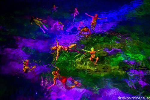 Луѓето пливаат во разнобојно  осветлената вода на затворен базен во Берн