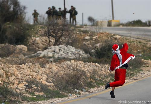 Палестинец како Дедо Мраз, фрла камења по Изралеската полиција