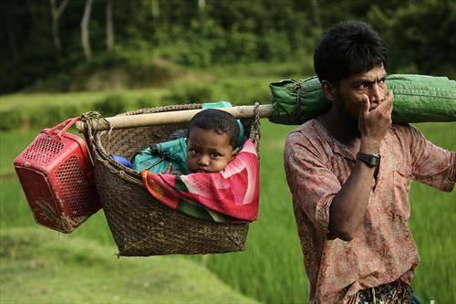 рохинга маж носи дете во кошница по бегството в о  Бангладеш