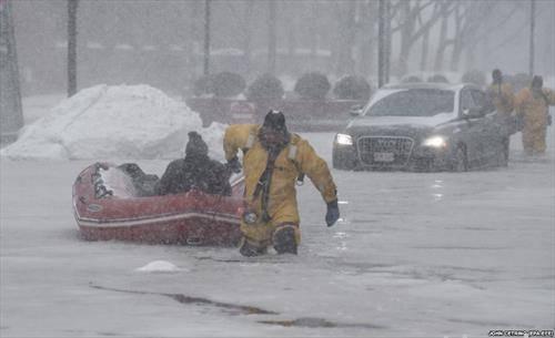 Спасувач влече гумен чамец по мразот на улиците на Бостон, во поларното невреме што зафати голем дел од САД