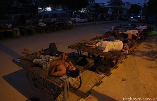 Продавачите и возачите на рикши спијат на отворено,  на жешкото летно утро во Карачи, Пакистан.