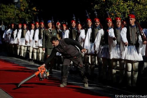 Човек го чисти црвениот килим поставен за пречекот на турскиот претседател Ердоган во официјална посета на Грција