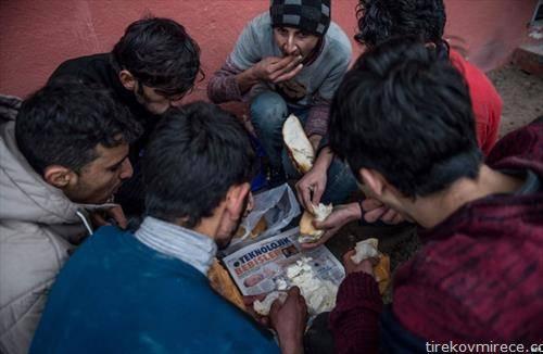 авганистански бегалци се хранат во турски бегалски камп
