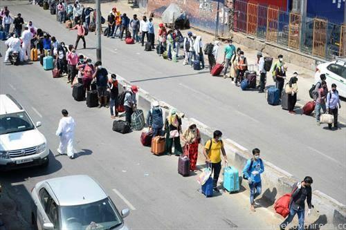 патници чекаат ред за железничка станица во њу делхи