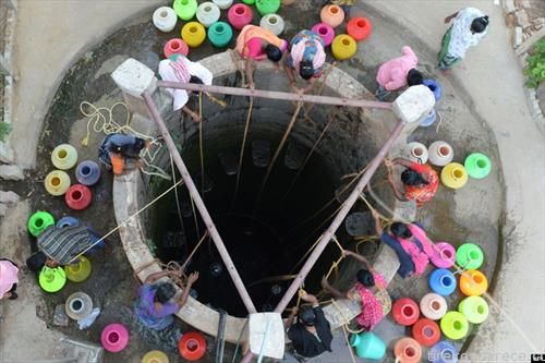 Индијки  полнат т вода за пиење од бунар на периферијата на Ченаи