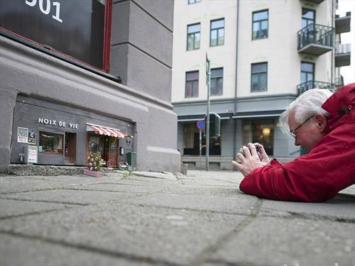 Човек легнат на земја додека го фотографира влезот на ресторанот за глодачи  во Малме, Шведска,