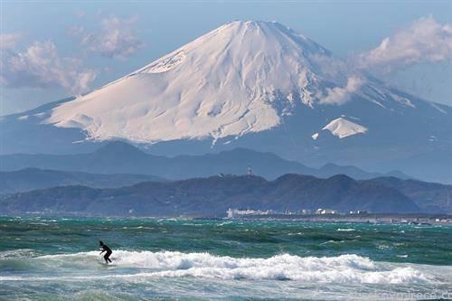 сурфер а во позадина планината и вулкан Фуџи