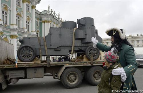 Актер облечен како рускиот цар Петар Велики му покажува на дете воено оклопно возило од 1919 година