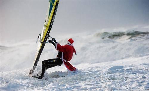 Серфер облачен како Дедо Мраз сурфа на снег, во Германија