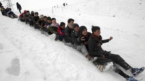 деца се радуваат на снег во Кабул