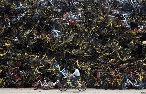 велосипедист во Кина, минува покрај отпад за велосипеди