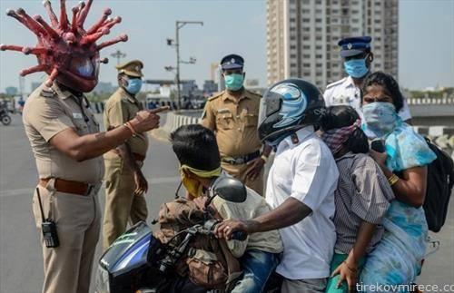 индиски полицаец маскиран како корона вирус предупредува семејство кое се вози на мотор