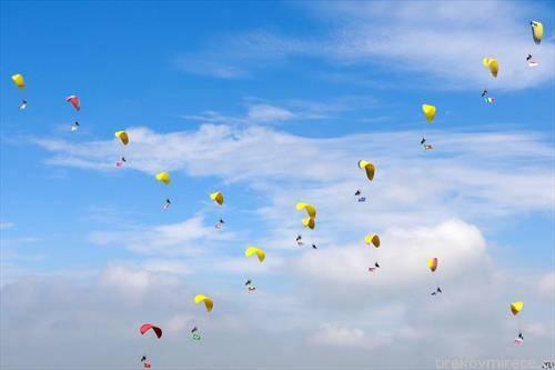 параглајдеристи изведуваат  уметнички скокови во Кина