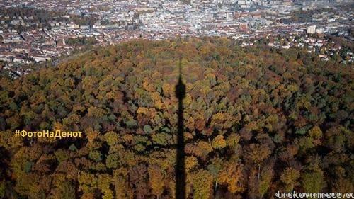 Сенката на 216 метри високата кула во Штутгарт  се оцртува врз есенски обоената шума во ноемвриски ден, а во заднина се гледа центарот на градот